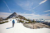 Photograph with rear view of male backpacker hiking to Needle Peak in winter, Hope, British Columbia, Canada