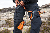 Mid section photograph of mountain climber putting on safety harness, Chilliwack, British Columbia, Canada
