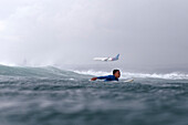 Surfer paddling on the sea as a plane flies overhead