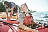 Photograph of young woman looking back at tandem kayak partner, Portland, Maine, USA