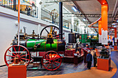 Two boys are standing next to a steam engine in technology and seafaring museum, Malmo, Southern Sweden, Sweden