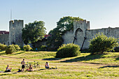 Young people with bicycles at the city wall of the old town of Visby, Schweden