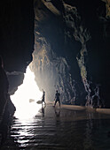 Two young men walking through a cave at the beach Praia da Amoreira,  Aljezur, Faro, Portugal