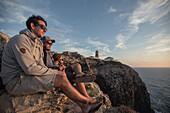 Four young men enjoying the sunset on a cliff at the beach Praia da Amoreira,  Aljezur, Faro, Portugal