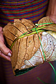 Woman holding wrapped organic leaves