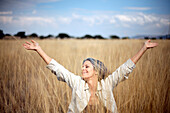 Carefree Caucasian woman standing in field of tall grass
