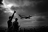 Soldiers pointing to flying old-fashioned airplane