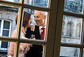 Well-dressed Caucasian couple drinking champagne behind window