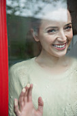 Caucasian woman smiling behind foggy window