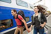 Caucasian couple running near train