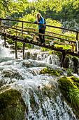 Older Caucasian woman on wooden footbridge admiring waterfall