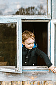 Caucasian boy opening window