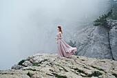 Caucasian woman wearing dress on rock in fog