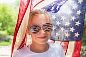 Caucasian girl wearing American flag sunglasses