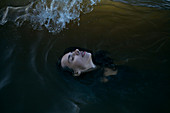 Caucasian woman floating in ocean with eyes closed