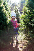 Excited Caucasian girl standing near trees