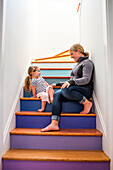 Caucasian mother and daughter laughing on multicolor staircase