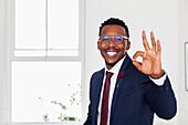 Black man gesturing okay in gallery