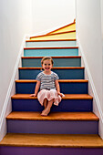 Portrait of smiling Caucasian girl sitting on multicolor staircase