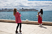 Young woman takes smartphone photograph of friend holding dog along seafront promenade, Split, Split-Dalmatia, Croatia