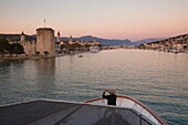 Man photographs Kamerlengo Castle and Old Town from bow of cruise ship MS Romantic Star (Reisebüro Mittelthurgau) at dusk, Trogir, Split-Dalmatia, Croatia