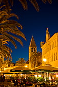 People at outdoor restaurants with church tower in Old Town at dusk, Trogir, Split-Dalmatia, Croatia