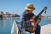 Street musician plays guitar and performs along seafront promenade, Trogir, Split-Dalmatia, Croatia