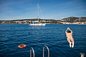 Man jumps from swimming platform of cruise ship MS Romantic Star (Reisebüro Mittelthurgau) into Adriatic Sea with sailboat behind, near Hvar, Split-Dalmatia, Croatia