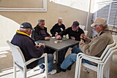 Five elderly men play cards while sitting on plastic chairs outside bar, Korcula, Dubrovnik-Neretva, Croatia