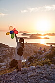 Young Asian woman holds colorful balloons and admires view across Lapad Peninsula and islands seen from hillside near top of Dubrovnik Gondola at sunset, Dubrovnik, Dubrovnik-Neretva, Croatia