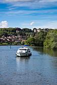 Le Boat Magnifique Hausboot während Bootstörn auf Fluss Petit Saône mit Stadt und Schloss Château Ray-sur-Saône dahinter, Ray-sur-Saône, Haute-Saône, Bourgogne Franche-Comté (Burgund), Frankreich, Europa