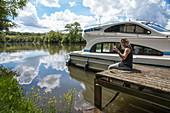 Junge Frau sitz auf Steg und hält Glas mit Weißwein vor Le Boat Elegance Hausboot an Anlegestelle während Bootstörn auf Fluss Petit Saône, Soing, Soing-Cubry-Charentenay, Haute-Saône, Bourgogne Franche-Comté (Burgund), Frankreich, Europa