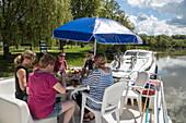 Friends enjoy lunch on deck of Le Boat Magnifique houseboat during cruise on Petit Saône river, Soing, Soing-Cubry-Charentenay, Haute-Saône, Bourgogne-Franche-Comté, France