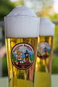 Two glasses of Räuberchen Blond beer brewed by Spessart Specht on terrace of Heimathenhof hotel and restaurant, Mespelbrunn Heimbuchenthal, Räuberland, Spessart-Mainland, Franconia, Bavaria, Germany