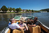 People enjoy motor boat excursion along Main river with river cruise ship Swiss Crown (Phoenix Kreuzfahrten) in distance, Marktheidenfeld, Spessart-Mainland, Franconia, Bavaria, Germany