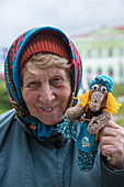 Cheerful elderly woman with self-knit handicraft doll, Uglich, Russia