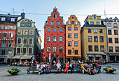 People sit on park benches in the main square Stortorget in the old town Gamla Stan, Stockholm, Sweden