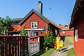 Woman with child between Sweden houses on the popular tourist island Sandhamn, Stockholm, Sweden