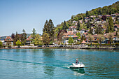 pleasure boater taking his boat out on lake thun, city of thun, canton of berne, switzerland