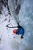 climber/mountaineer planting his ice axe in an ice cascade, golsjuvet falls, gol, region of hemsedal, buskerud, norway