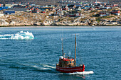 boat in front of the icebergs from the jakobshavn glacier, sermeq kujalleq, and the town of ilulissat, greenland