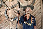 Wangchah Wangsa, Naga headhunter, with tattooed face and Naga tribal necklace, holding hunting spear, Longwa village, Nagaland, India, Asia