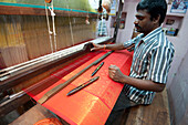 Silk weaver at his loom in his house, weaving sought after red and gold Kanchipuram silk sari, Kanchipuram, Tamil Nadu, India, Asia