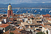 France, Var department, a large view on the old roofs and the church of the city of Saint-Tropez with in background yachting boats