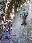North Italy, Trentino,Arco,via ferrata of the Sallagoni river, a man wearing a harness climbs on a cliff equipped with a via ferrata