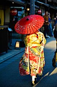 Japanese woman in a traditional kimono dress with a red umbrella,Kyoto, Japan,Asia