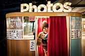 Woman wearing knitted hat and glasses behind Photo booth curtain, Germany