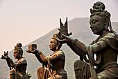 Supporting figures make offerings to Big Buddha, Po Lin Monastery, Ngong Ping, Lantau Island, Hong Kong, China, Asia