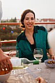 Happy woman sitting at outdoor lunch table on patio