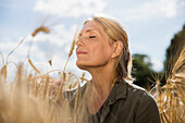 Thoughtful smiling woman with closed eyes resting amidst crops at farm on sunny day